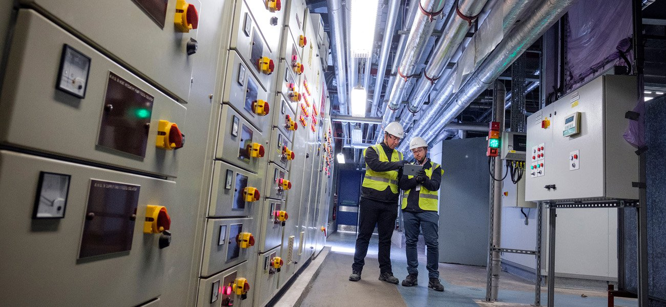 Engineers check plant room drawings on a tablet